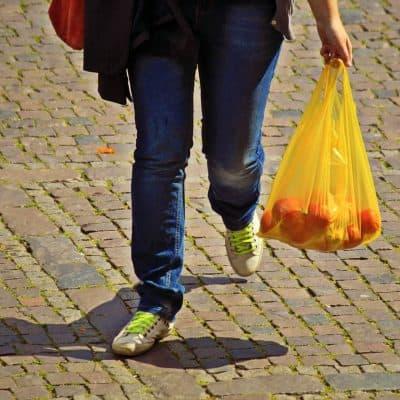 אישה מחזיקה שקית ניילון עם תפוזים